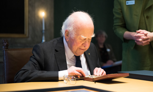 Peter Higgs looking at his Nobel Medal during his visit to the Nobel Foundation