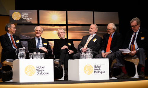 Six Nobel Laureates in a panel discussion at the 2013 Nobel Week Dialogue on 9 December 2013. From left: 1997 Physics Laureate Steven Chu, 2004 Physics Laureate David Gross, 2000 Chemistry Laureate Alan Heeger, 1988 Chemistry Laureate Hartmut Michel, 1995 Chemistry Laureate Mario Molina and 1984 Physics Laureate Carlo Rubbia