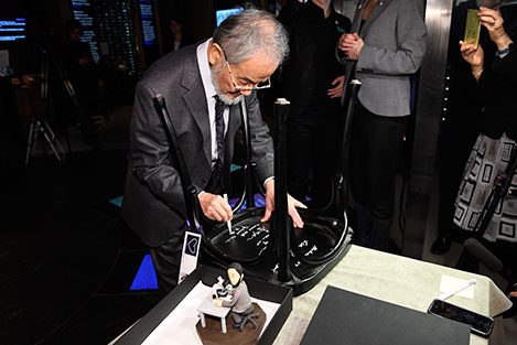 Yoshinori Ohsumi autographs a chair