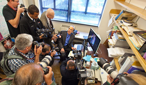 Saul Perlmutter in his office, surrounded by journalists