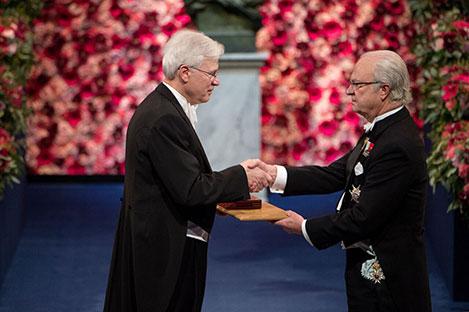 Bengt Holmström  receiving his Prize from H.M. King Carl XVI Gustaf of Sweden