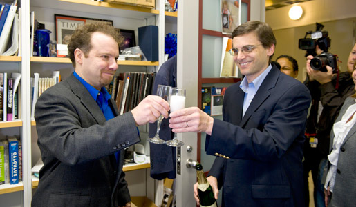 Adam Riess celebrating with a glass champagne with colleague Dan Reich