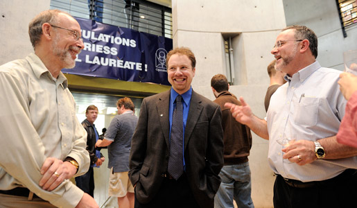 Adam Riess, center, is congratulated by colleagues Julian Krolik and Charles Bennett