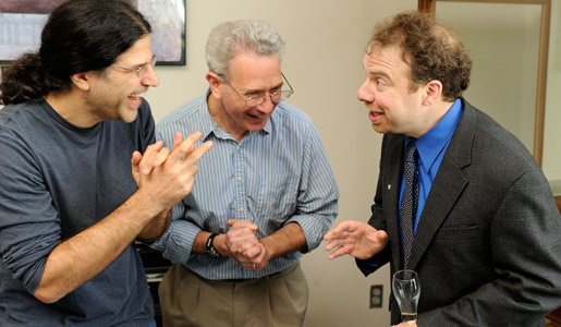 Adam Riess, right, is congratulated by colleagues after the announcement of the 2011 Nobel Prize in Physics