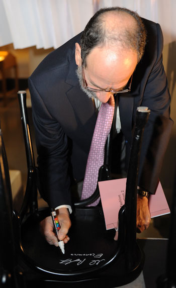 Like many Laureates before him, Alvin E. Roth autographs a chair at Bistro Nobel at the Nobel Museum in Stockholm