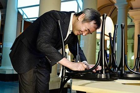 Like many Nobel Laureates before him, Takaaki Kajita autographs a chair at Bistro Nobel at the Nobel Museum in Stockholm.